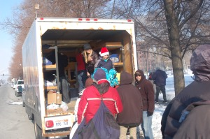 Volunteers help the homeless from the back of the ICOR truck on a bitterly cold afternoon last Saturday.  (Photo by John G. Miller)