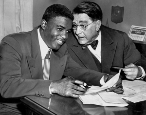 Jackie Robinson with Branch Rickey as Robinson signs his contract, becoming the first black player in Major League Baseball history.