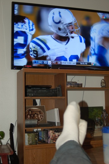 Football on TV with feet propped up. Finally, a chance to rest and recuperate after an exhausting few weeks spent moving. (Photo by John G. Miller)